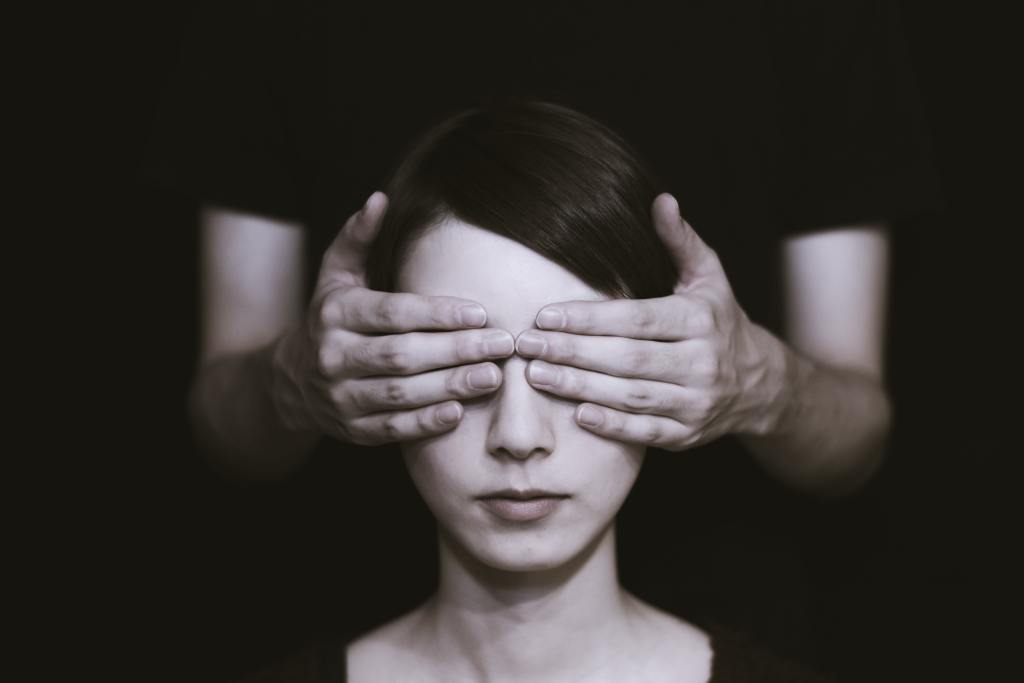 Black and white image of woman's eyes covered by man's hands.