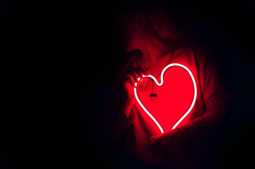 A woman holding a glowing red heart in the darkness.