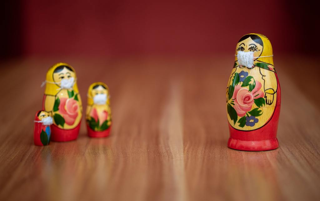 A family of wooden dolls wearing masks, with the mother doll standing apart from her children.