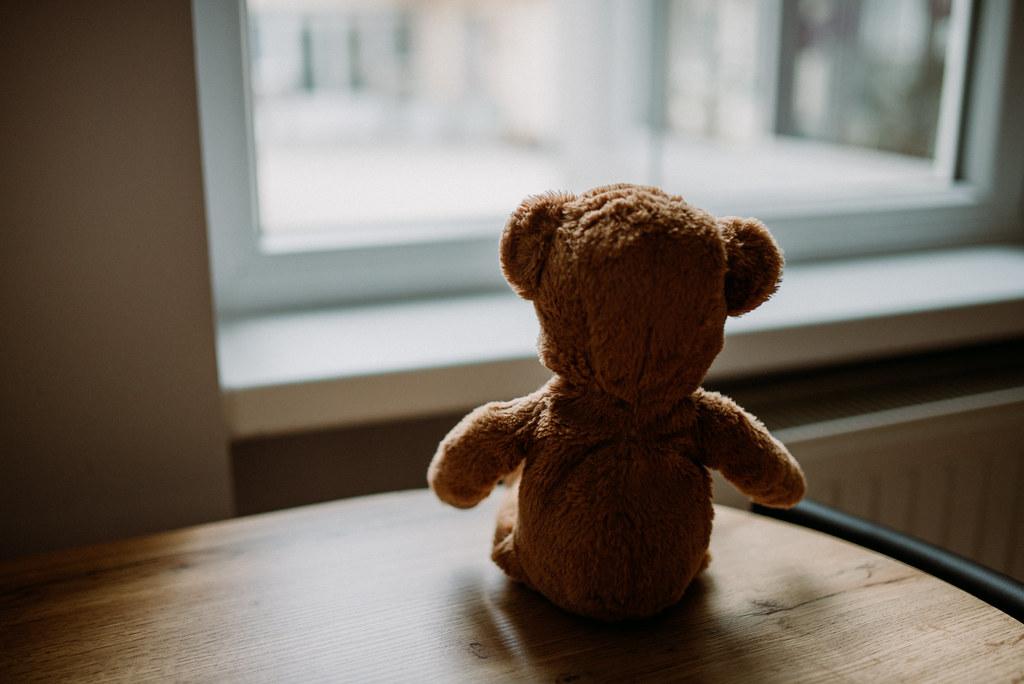 Tiny teddy bear facing the window forlornly.