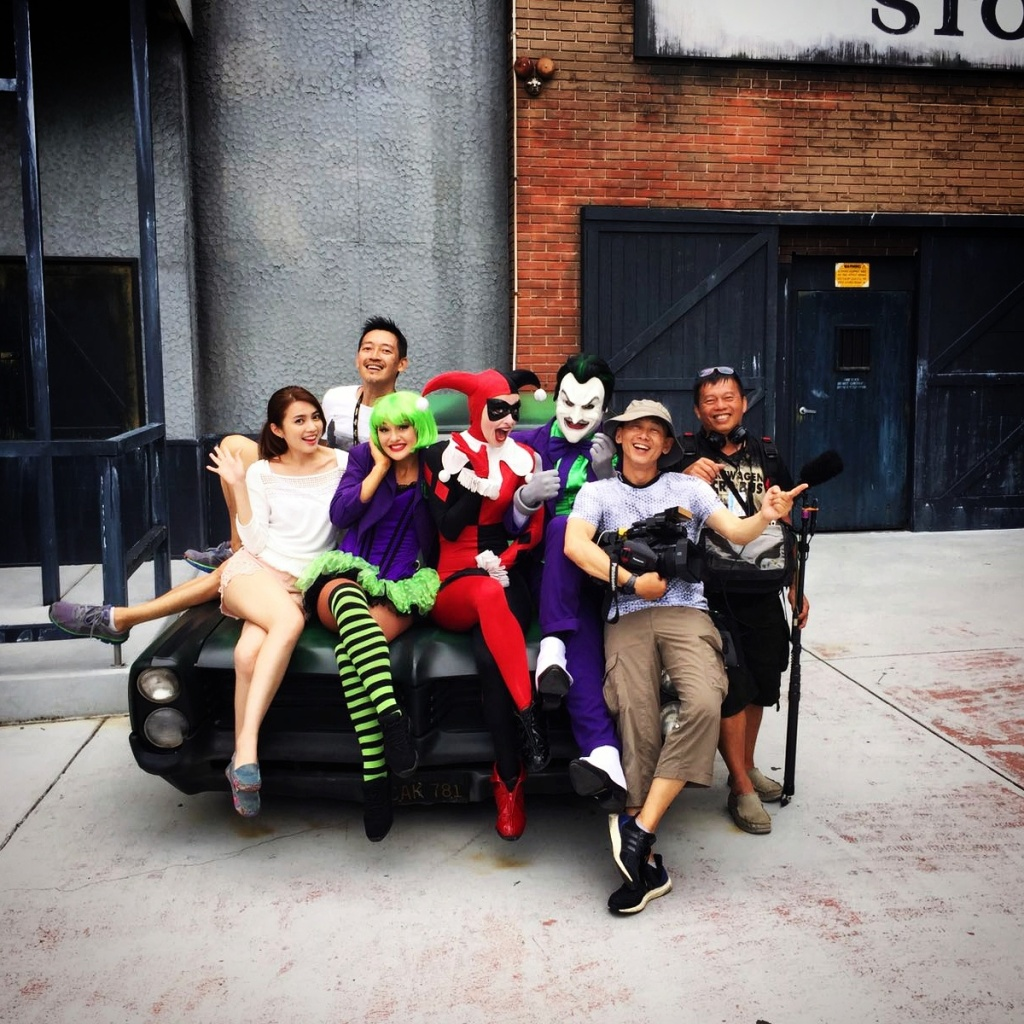 The crew (Director, Cameraman, Soundman) and I posing with the three villains (Green-haired female villain - Don't know who she is, Harley Quinn and The Joker) on top of a black and green car.